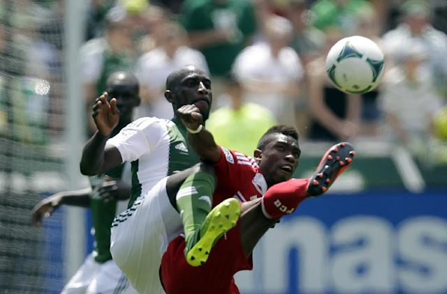 FC Dallas midfielder Fabian Castillo, right, kicks the ball away from Portland Timbers forward Frederic Piquionne during the first half of an MLS soccer game in Portland, Ore., Saturday, June 15, 2013. (AP Photo/Don Ryan)