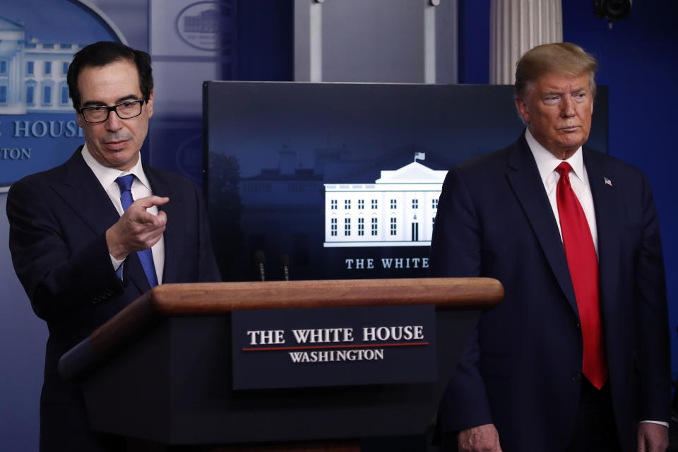 President Donald Trump listens as Treasury Secretary Steven Mnuchin speaks about the coronavirus in the James Brady Press Briefing Room at the White House, Monday, April 13, 2020, in Washington. (AP Photo/Alex Brandon)