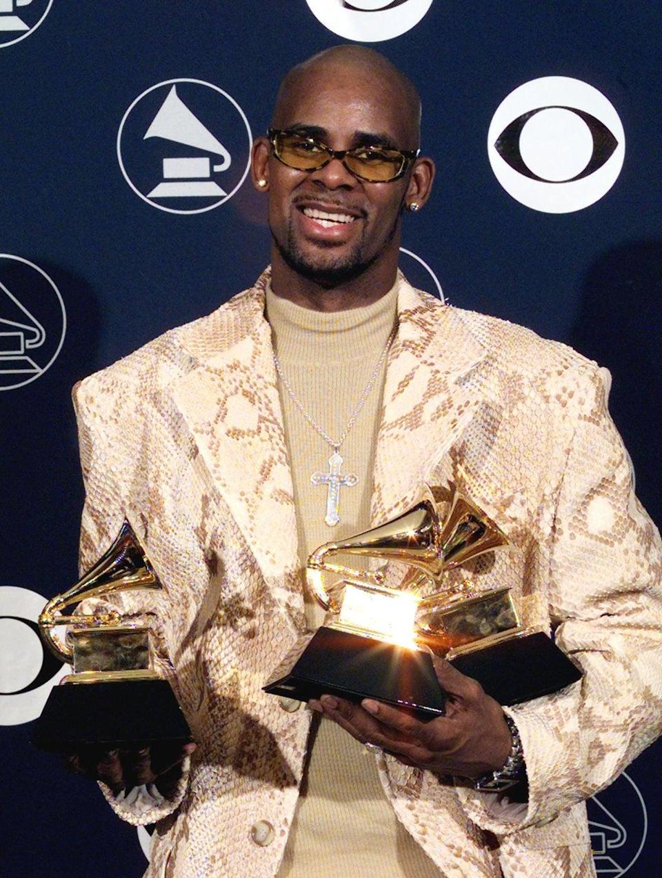 R Kelly holds his three Grammy Awards in  1998 (AFP via Getty Images)