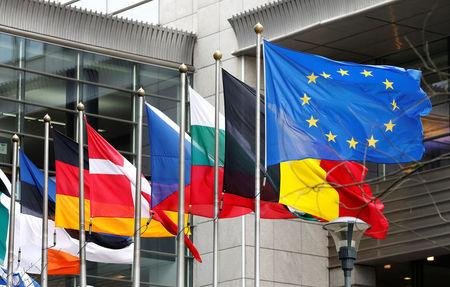 European and national flags fly outside the European Parliament while European Commission President Jean-Claude Juncker presents a white paper in Brussels