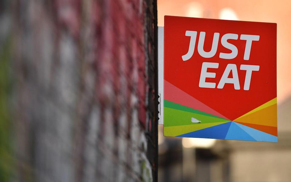 a sign for Just Eat, a food delivery service can be seen above a restaurant in London - BEN STANSALL/AFP