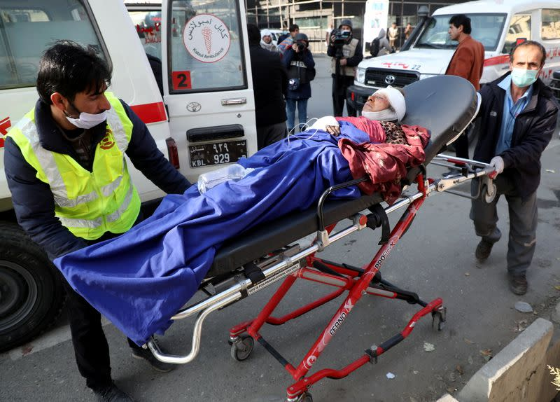 An injured person is carried to a hospital after rockets hit residential areas in Kabul