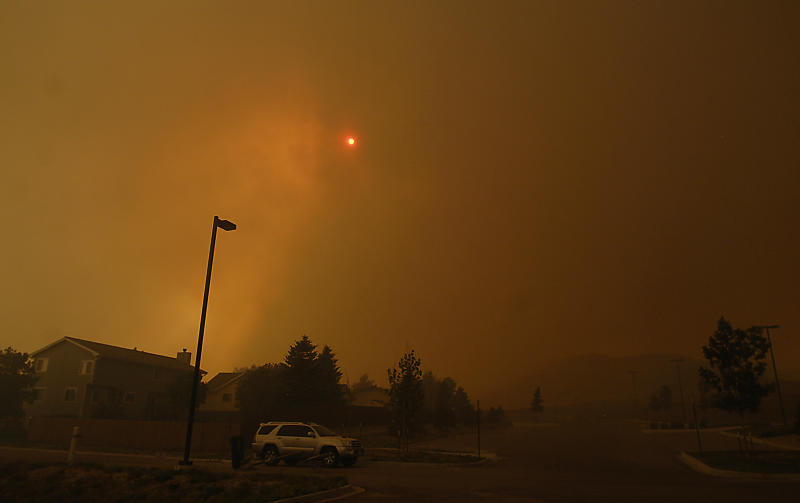 The skies are orange as flames from the Waldo Canyon Fire race through a neighborhood in west  Colorado Springs, Colo. on Tuesday, June 26, 2012 leaving a trail of destruction, burning homes and buildings in its path. Heavily populated areas in the fire's path have been affected.   (AP Photo/Bryan Oller)