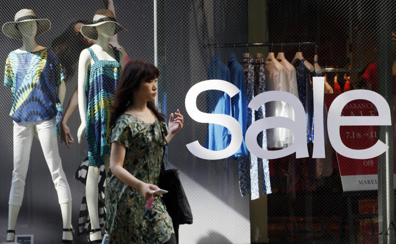FILE - In this July 2, 201 file photo, a woman walks by a clothing store on sale in Tokyo. Japan released data on Friday, Aug. 30, 2013 showing its economic recovery gained momentum in July, as manufacturing accelerated and consumer prices rose for a second straight month, despite weaker household spending and retail sales. (AP Photo/Koji Sasahara, File)