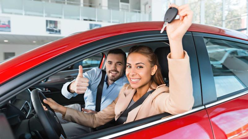 Young couple sitting inside new car they just bought in dealership