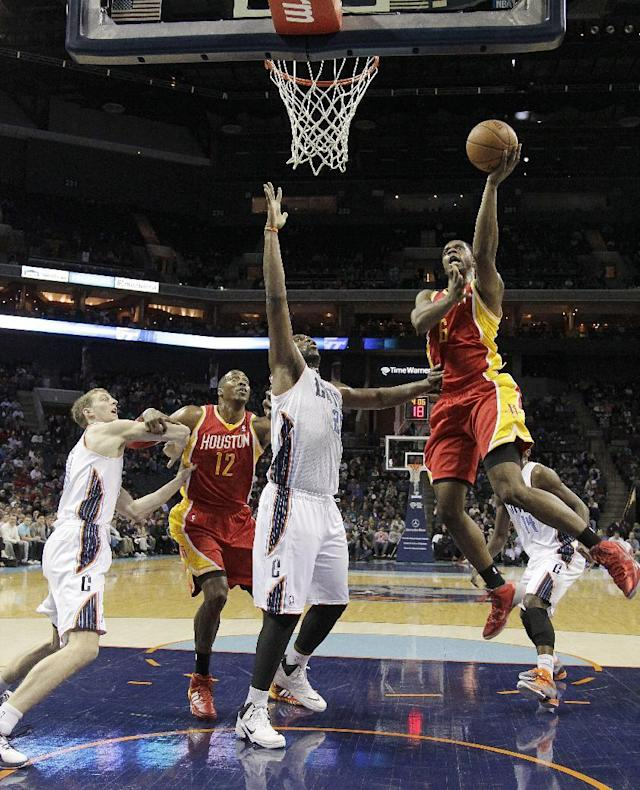 Houston Rockets' Terrence Jones (6) drives in for the layup over Charlotte Bobcats' Al Jefferson (25) as Charlotte Bobcats' Cody Zeller, left, battles Houston Rockets' Dwight Howard (12) for position during the first half of an NBA basketball game in Charlotte, N.C., Monday, March 24, 2014. (AP Photo/Bob Leverone)