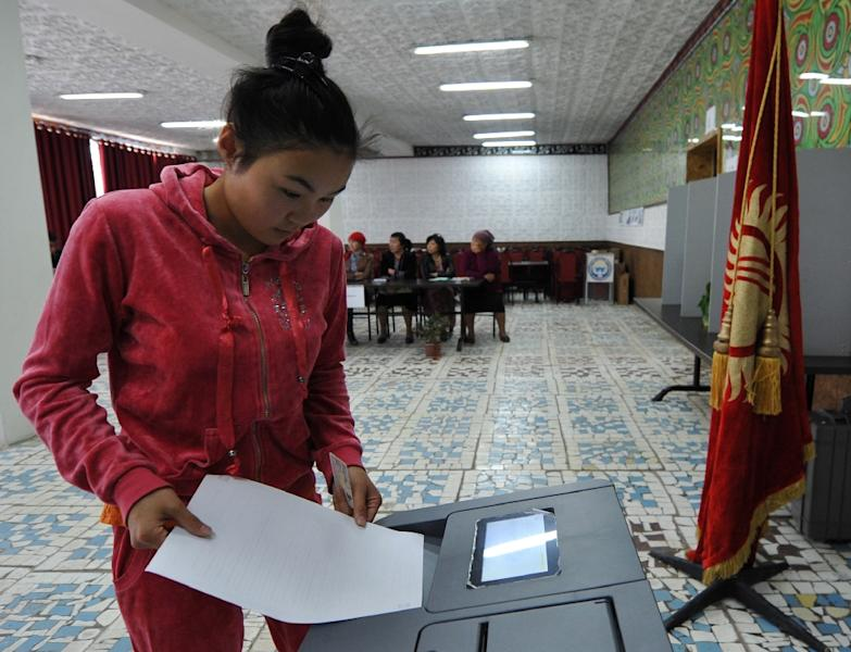A woman votes at a polling station during Kyrgyz parliamentary elections in the village of Kara-Zhigach, outside Bishkek, on October 4, 2015 (AFP Photo/Vyacheslav Oseledko)