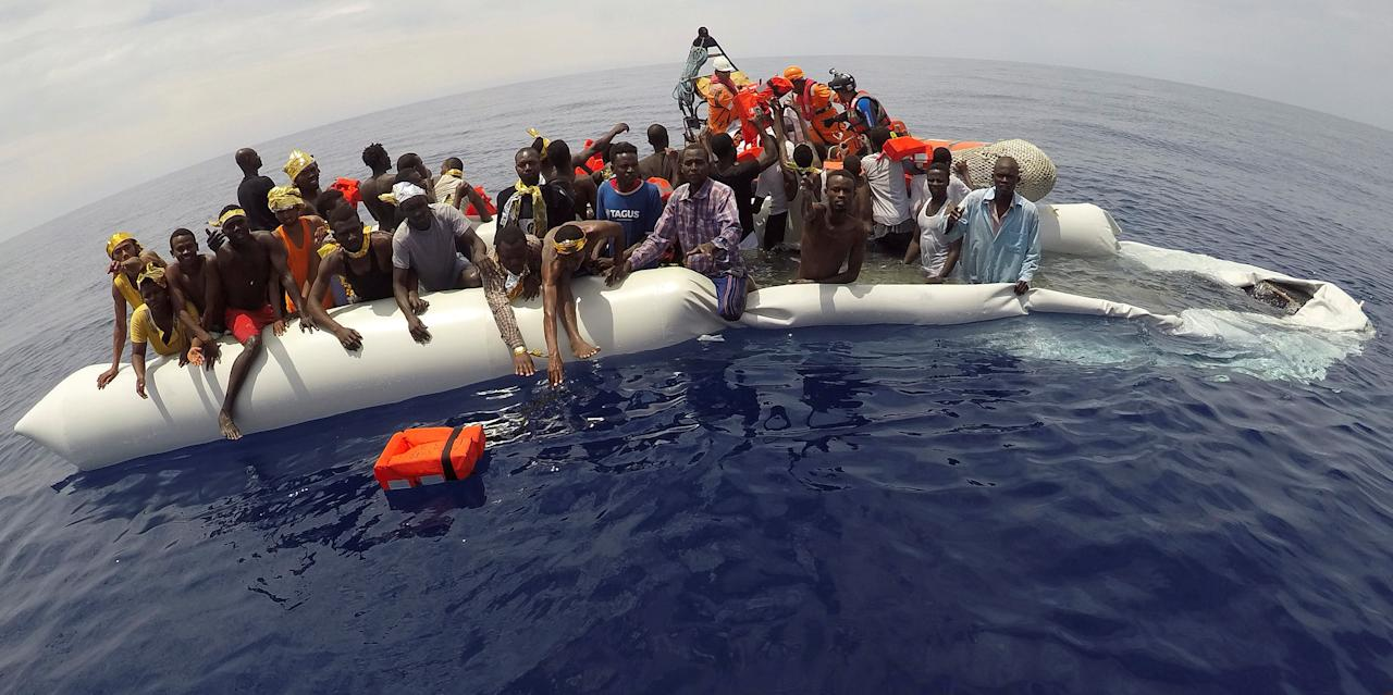 "FILE PHOTO: Migrants on a dinghy are rescued by ""Save the Children"" NGO crew from the ship Vos Hestia in the Mediterranean sea off Libya coast, June 17, 2017.  REUTERS/Stefano Rellandini/File Photo"