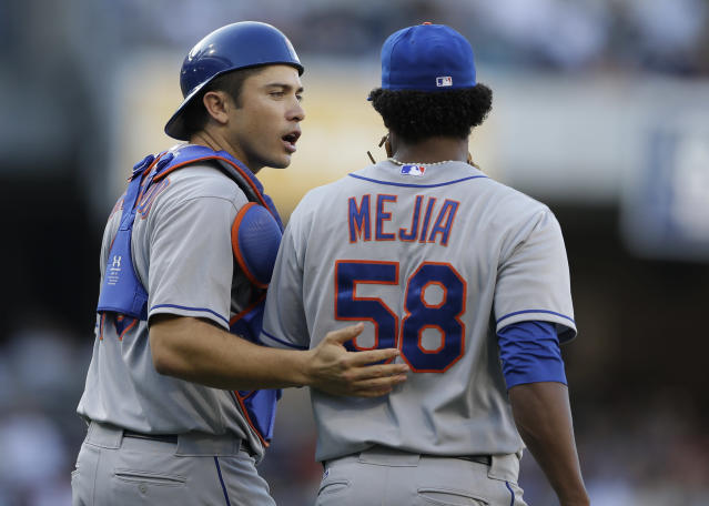 New York Mets catcher Travis d'Arnaud, left, talks with starting pitcher Jenrry Mejia, right, as they walk back to the mound while playing San Diego Padres during the second inning in a baseball game on Saturday, Aug. 17, 2013, in San Diego. (AP Photo/Gregory Bull)
