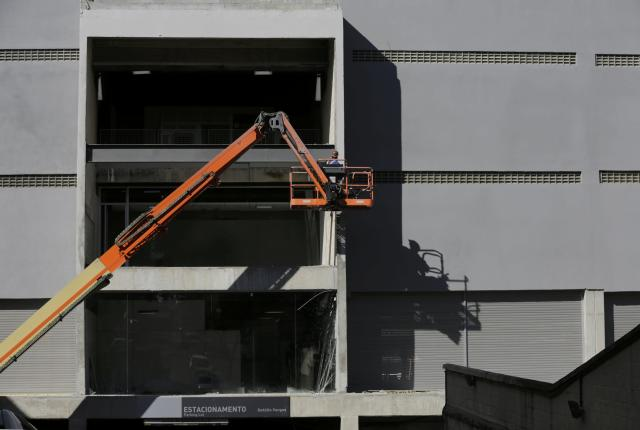 A construction worker paints a wall at the Arena Baixada soccer stadium in Curitiba, June 13, 2014. The stadium will host the first of four 2014 World Cup matches on June 16. REUTERS/Henry Romero (BRAZIL - Tags: BUSINESS CONSTRUCTION SOCCER SPORT WORLD CUP)