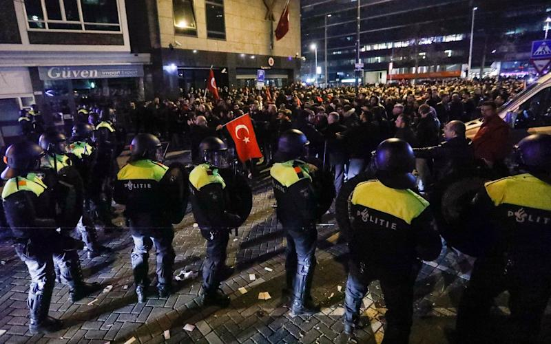 Demonstrators face Dutch riot police outside the Turkish consulate in Rotterdam - Credit: Reuters