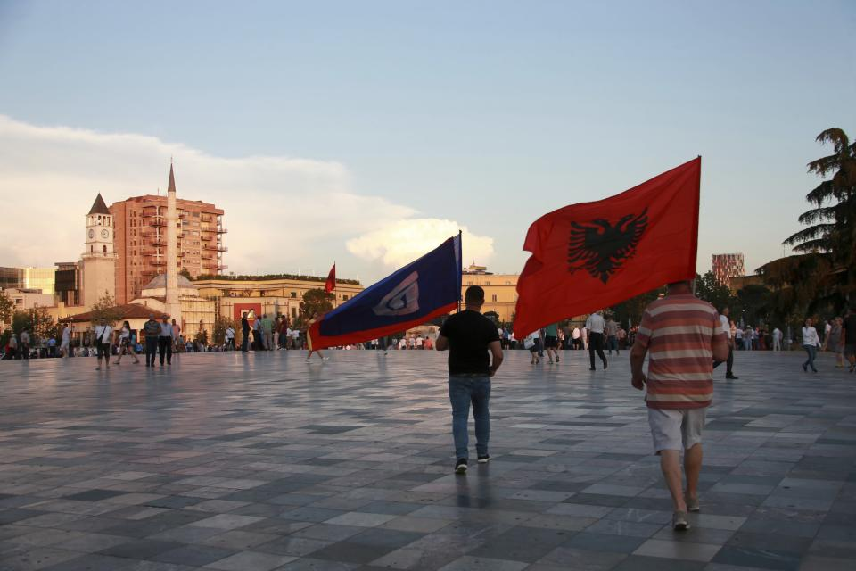 Antigovernment protesters hold an Albanian, right, and main opposition Democratic party flags during a rally at Skanderbeg square in Tirana, Friday, June 21, 2019. The opposition is boycotting the local elections planned for June 30 and has threatened to disrupt them.(AP Photo/Hektor Pustina)