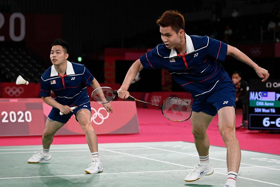Malaysia's Soh Wooi Yik (right) hits a shot next to partner Aaron Chia in their men's doubles badminton bronze-medal match against Indonesia's Mohammad Ahsan and Hendra Setiawan at the 2020 Tokyo Olympics.