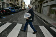A man wearing a face mask protection to prevent the spread of the coronavirus, crosses a road while carrying a Spanish newspaper reporting on President-elect Joe Biden winning the US presidential election, in Pamplona, northern Spain, Sunday, Nov. 8, 2020. (AP Photo/Alvaro Barrientos)