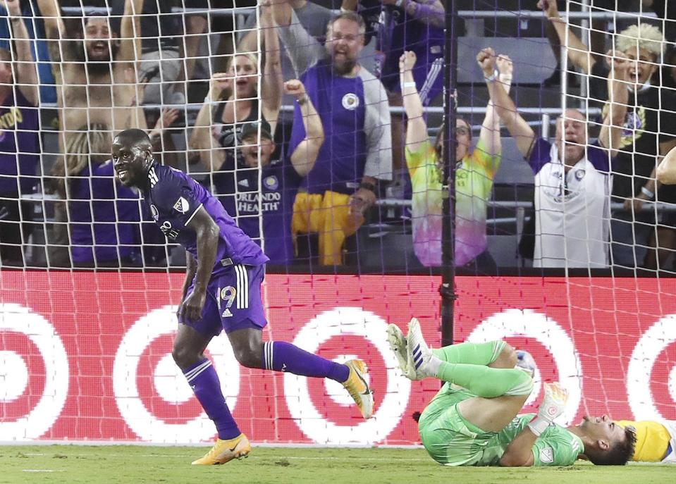 Orlando player Benji Michel celebrates in front of fans and fallen San Jose goalkeeper J.T. Marcinkowski, right, after scoring a goal during a MSL soccer match in Orlando, Fla., on Tuesday, June 22, 2021. (Stephen M. Dowell /Orlando Sentinel via AP)