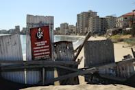 """FAMAGUSTA, CYPRUS - MARCH 06: Former, decaying hotel buildings stand beyond a makeshift barrier and a Turkish military sign inside the """"Forbidden Zone"""" of Varosha district on March 6, 2017 in Famagusta, Cyprus. Hundrds of buildings inside Varosha district, which was once a prime Cypriot resort, stand abandoned and decaying in a zone the Turkish military has sealed off ever since Varosha residents fled in the 1974 war. Cyprus has been divided into a Greek south and Turkish north ever since the brief but devastating war of 1974. Since then United Nations peacekeepers have maintained a buffer zone that runs through the capital city of Nicosia and across the entire island to keep the factions apart. In the south the Greek-dominated Republic of Cyprus is internationally-recognized and a member of the European Union, while in the north the self-proclaimed Turkish Republic of North Cyprus (TRNC) is recognized only by Turkey, which also has tens of thousands of troops stationed there. Negotiations over possible reunification have made strident progress over the last few years, though they have stalled in recent months. (Photo by Sean Gallup/Getty Images)"""