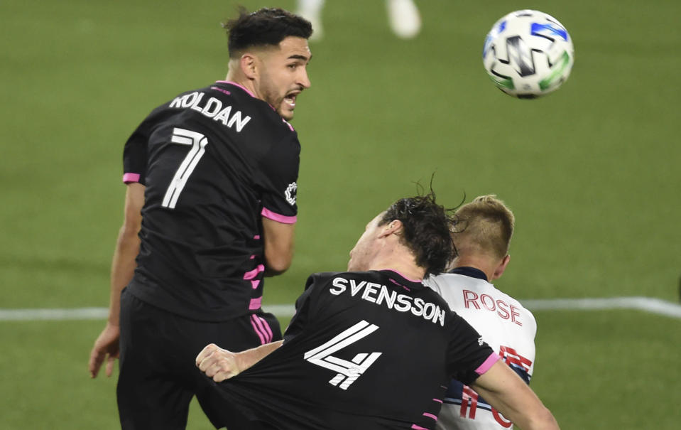 Seattle Sounders midfielder Cristian Roldan, left, heads the ball next to defender Gustav Svensson, center, and Vancouver Whitecaps midfielder Andy Rose during the second half of an MLS soccer match in Portland, Ore., Tuesday, Oct. 27, 2020. (AP Photo/Steve Dykes)