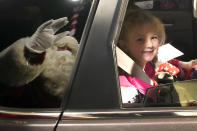 Brynn Brennan smiles at a social distant Santa as she rides past Santa's Garage on the roof of a parking garage next to Soldier Field in Chicago on Dec. 10, 2020. In this socially distant holiday season, Santa Claus is still coming to towns (and shopping malls) across America but with a few 2020 rules in effect. (AP Photo/Charles Rex Arbogast)