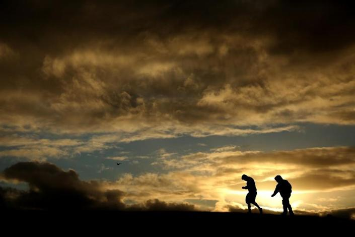 VENICE, CA - JANUARY 22, 2021 - Aiden Martinez, 10, left, and his cousin Jovanny Martinez, 12, climb on top of a berm framed by storm clouds in Venice Beach on January 22, 2021. Three consecutive storm systems will move into the Southland beginning Friday, according to the National Weather Service. Temperatures will drop by as much as 40 degrees. Rain will be light Friday and Saturday, but is expected to pick up by Sunday, while snow levels could drop too as low as 2,000 feet Sunday and Monday nights. (Genaro Molina / Los Angeles Times)