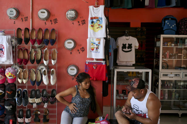 """In this July 19, 2018 photo, Adalicia Montecinos, 7-months pregnant, sits with her husband Rolando Bueso Castillo, at her clothing stall at a market in La Libertad, Honduras. Montecinos rents the stand where she sells Nike baseball hats, """"California Dreaming"""" T-shirts and jewelry. Her husband makes a living driving a minibus. (AP Photo/Esteban Felix)"""