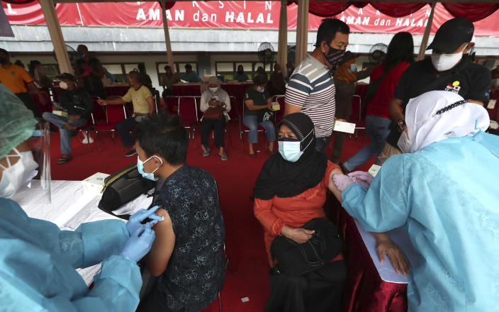 People receive a shot of the Sinovac vaccine for COVID-19 during a vaccination campaign at the Patriot Candrabhaga Stadium in Bekasi on the outskirts of Jakarta, Indonesia, Thursday, July 1, 2021.(AP Photo/Achmad Ibrahim)