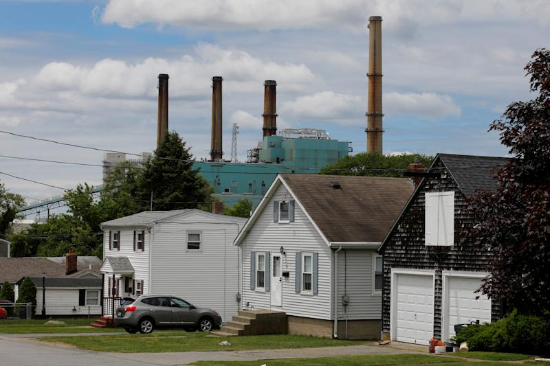 The Brayton Point power plant, a coal-fired power plant that was shut down June 1, rises behind houses in Somerset, Massachusetts. (Brian Snyder / Reuters)