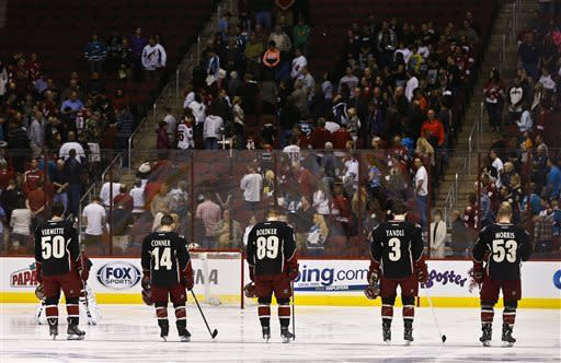 Phoenix Coyotes' Antoine Vermette (50), Chris Conner (14), Mikkel Boedker (89), of Denmark, Keith Yandle (3), and Derek Morris (53) stand along with the crowd for a moment of silence for the victims of the bombing at the Boston Marathon prior to an NHL hockey game between the San Jose Sharks and the Coyotes, on Monday, April 15, 2013 in Glendale, Ariz. (AP Photo/Ross D. Franklin)
