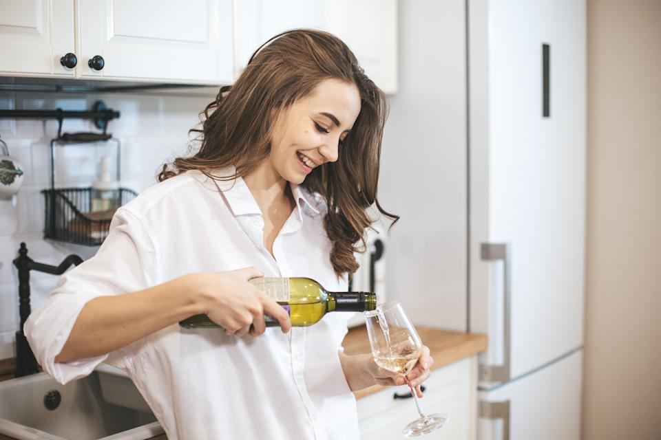 Young woman with glass of wine at home. Female person relax drinking wine at kitchen.