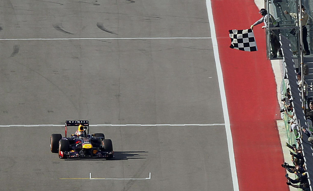Red Bull Formula One driver Sebastian Vettel of Germany takes the checkered flag to win the Austin F1 Grand Prix at the Circuit of the Americas in Austin November 17, 2013. REUTERS/Mike Stone (UNITED STATES - Tags: SPORT MOTORSPORT F1)