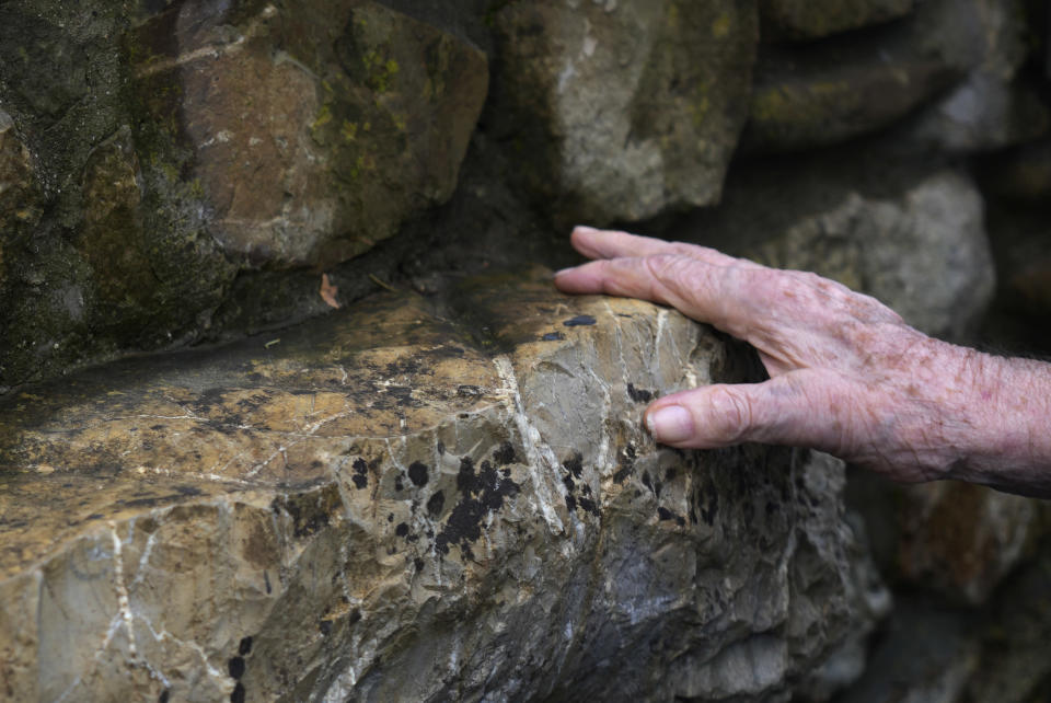 A 97 year old retired American soldier Martin Adler touches a rock where he was sitting with Giulio, Mafalda, and Giuliana Naldi to take picture after saving them during WWII, in Monterenzio, near Bologna, Italy, Monday, Aug. 23, 2021. For more than seven decades, Martin Adler treasured a back-and-white photo of himself as a young soldier with a broad smile with three impeccably dressed Italian children he is credited with saving as the Nazis retreated northward in 1944. The 97-year-old World War II veteran met the three siblings -- now octogenarians themselves -- in person for the first time on Monday, eight months after a video reunion. (AP Photo/Antonio Calanni)