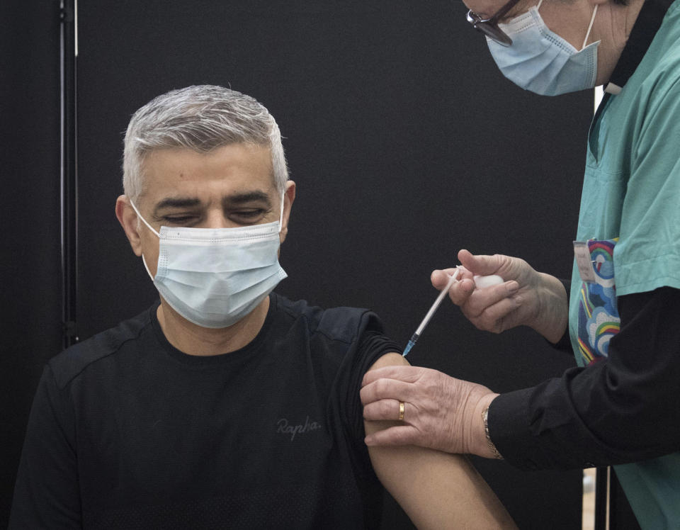 Mayor of London Sadiq Khan receives his first dose of the Pfizer coronavirus vaccine administered by Dr. Sue Clarke at a COVID-19 vaccination clinic at the Mitcham Lane Baptist Church in south London, Friday Feb. 19, 2021. (Stefan Rousseau/PA via AP)