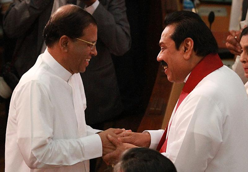 Sri Lanka's President Maithripala Sirisena (L) shakes hands with former president Mahinda Rajapakse during a ceremony to swear in Ranil Wickremesinghe as the country's new prime minister, in Colombo, on August 21, 2015 (AFP Photo/Ishara S. Kodikara)