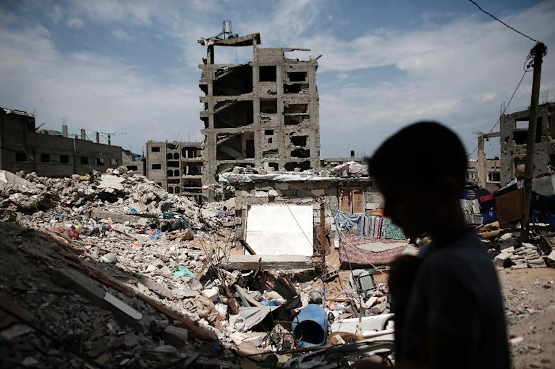 A Palestinian boy walks over the rubble of his family's former house in Gaza City's Shujaiya neighbourhood on May 11, 2015 (AFP Photo/Thomas Coex)