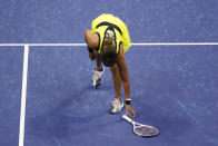 Naomi Osaka, of Japan, picks up her racket after throwing it down during a match against Leylah Fernandez, of Canada, at the third round of the US Open tennis championships, Friday, Sept. 3, 2021, in New York. (AP Photo/Frank Franklin II)