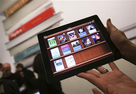File photo of a woman holding up an iPad with the iTunes U app after a news conference introducing a digital textbook service in New York