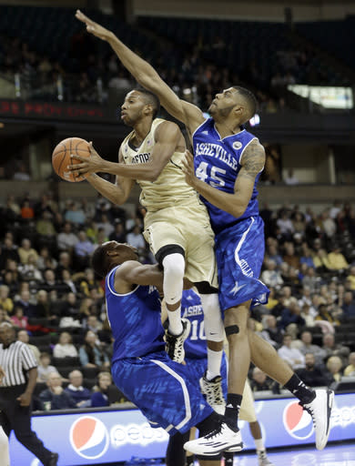 Wake Forest's Madison Jones, center, drives between UNC Asheville's Jaleel Roberts, right, and Sam Hughes, left, during the first half of an NCAA college basketball game in Winston-Salem, N.C., Friday, Nov. 14, 2014. (AP Photo/Chuck Burton)