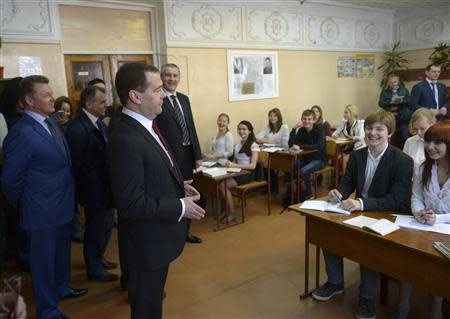 Russia's Prime Minister Dmitry Medvedev (C, front) visits an upper secondary school in the Crimean city of Simferopol, March 31, 2014. REUTERS/RIA Novosti/Alexander Astafyev/Pool
