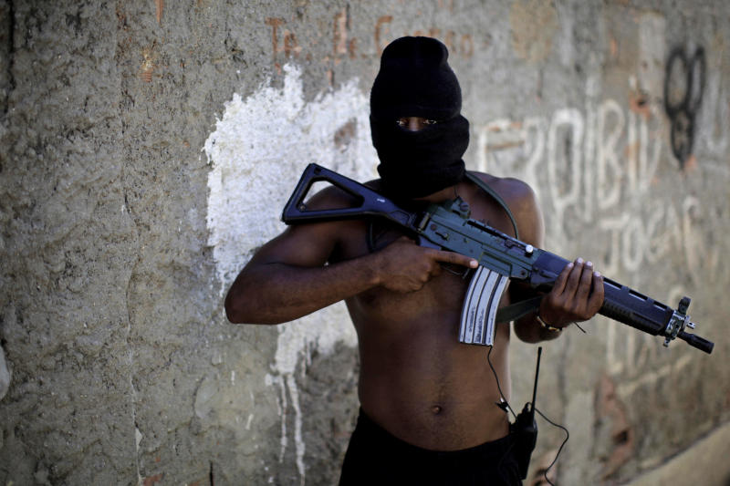 "In this photo taken Nov. 7, 2010, an alleged drug trafficker who identified himself as ""Jogador"" poses for a photo with a weapon as he stands in an alley at a slum in western Rio de Janeiro, Brazil. Rio is seeing violent, chaotic days. Armed men have set up roadblocks in key areas _ a highway leading to the international airport, an avenue running by the state government's headquarters, quiet streets in wealthier neighborhoods _ letting loose rifle fire, tossing grenades. Police responded by invading more than 20 slums and engaging traffickers in massive shootouts. Authorities now control one of the most fortified slums where traffickers long ruled with impunity, and are preparing to invade another that many fear will ignite an even bloodier battle. (AP Photo/Felipe Dana)"