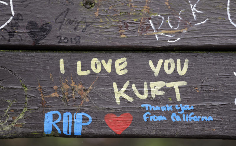 Messages honoring the late Nirvana frontman Kurt Cobain are written on a park bench, Friday, April 5, 2019, in Seattle. People gathered throughout the day at Viretta Parkin in Seattle, Friday, leaving flowers, candles and written messages on the 25th anniversary of Cobain's death. Cobain, whose band Nirvana rose to global fame amid Seattle's grunge rock years of the early 1990s, shot himself on April 5, 1994 in his home near Lake Washington. (AP Photo/Elaine Thompson)