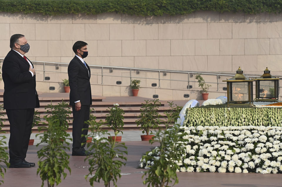 U.S. Secretary of State Mike Pompeo, left, and Secretary of Defence Mark Esper pay their tributes at the National War Memorial in New Delhi, India, Tuesday, Oct. 27, 2020. In talks on Tuesday with their Indian counterparts, Pompeo and Esper are to sign an agreement expanding military satellite information sharing and highlight strategic cooperation between Washington and New Delhi with an eye toward countering China. (Jewel Samad/Pool via AP)