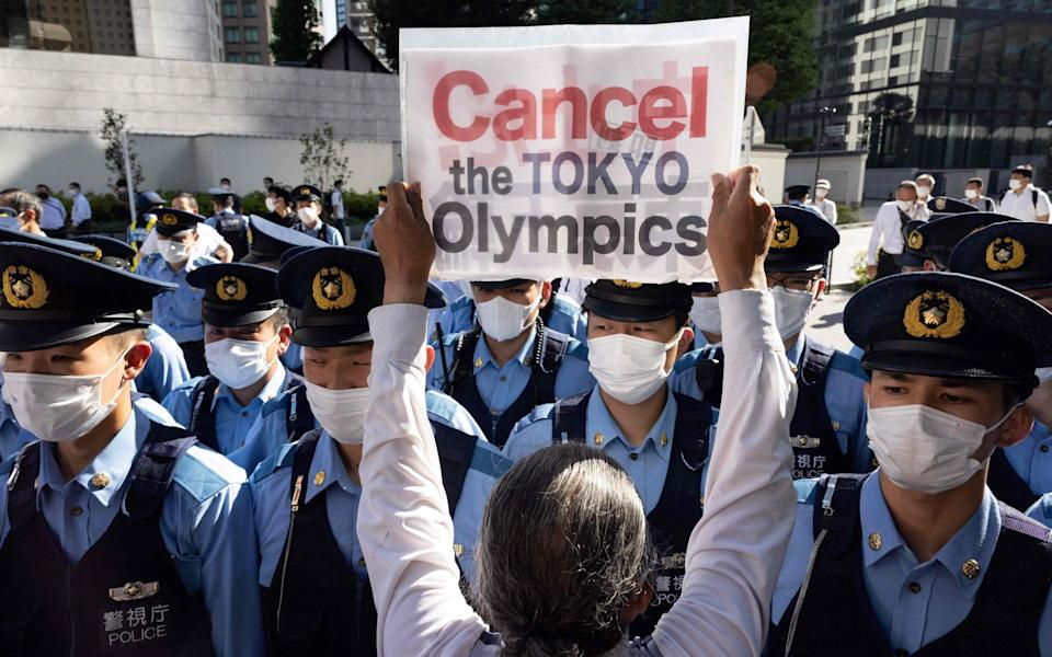 Police officers block a small group of activists as they walk towards the hotel where International Olympic Committee president Thomas Bach is staying for a demonstration in Tokyo on July 17, 2021, calling for the cancellation of the Tokyo 2020 Olympic Games - GETTY IMAGES