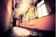 <p>An empty chair is all that remains in this abandoned hospital corridor.</p>