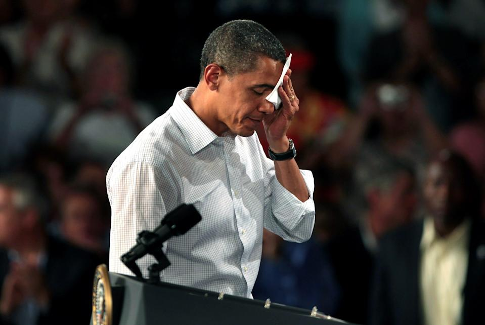President Barack Obama wipes his brow while holding a health care town hall meeting in the Central High School gym on August 15, 2009 in Grand Junction, Colorado.