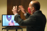 Defendant Gordon Searles appears on video for a bail hearing as Defense Attorney Joe Fricano, right, speaks at Manchester, N.H. District Court, Monday, April 12, 2021, in connection with sexual abuse allegations at the Sununu Youth Services Center, a state-run youth detention center. (AP Photo/Elise Amendola, Pool)