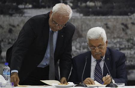 Palestinian chief negotiator Saeb Erekat helps Palestinian President Mahmoud Abbas as he signs international conventions during a meeting with Palestinian leadership in Ramallah