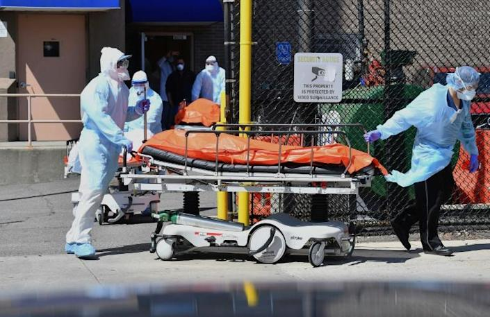 Medical staff move bodies from the Wyckoff Heights Medical Center to a refrigerated truck in Brooklyn, New York (AFP Photo/Angela Weiss)