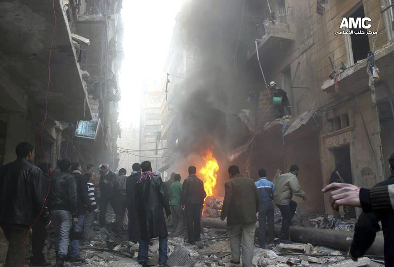 In this Sunday, Dec. 15, 2013 citizen journalism image provided by Aleppo Media Center, AMC, which has been authenticated based on its contents and other AP reporting, Syrians gather around damaged buildings while others try to extinguish fires following a Syrian government airstrike in Aleppo, Syria. The Britain based Syrian Observatory for Human Rights said Monday that dozens of children were among scores killed in airstrikes on several opposition areas a day earlier. (AP Photo/Aleppo Media Center, AMC)