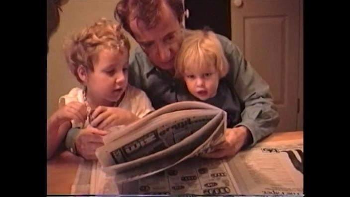 Young Dylan and Ronan Farrow sit in Woody Allen's lap, looking at a newspaper.