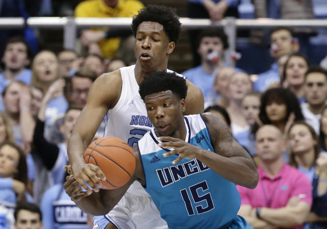 North Carolina's Sterling Manley guards UNC Wilmington's Devontae Cacok (15) during the first half of an NCAA college basketball game in Chapel Hill, N.C., Wednesday, Dec. 5, 2018. (AP Photo/Gerry Broome)
