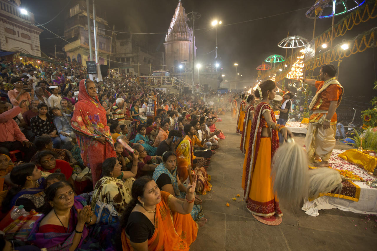 <p>A Hindu priest prays as women devotees stand during the Ganga Dussehra festival on the banks of the River Ganges in Varanasi, India, Thursday, May 24, 2018. Hindus across the country celebrate Ganga Dussehra by worshiping the River Ganges, which is considered the most sacred and the holiest river for Hindus. (AP Photo/Rajesh Kumar Singh) </p>
